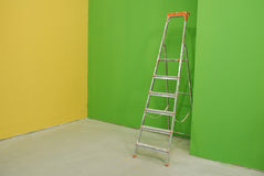 Ladder by painted walls Stock Images