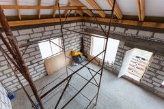 Ladder, parts of scaffolding and construction material on the floor during on the remodeling, renovation, extension, restoration,. Reconstruction and stock images