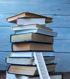 Ladder on pile of old books on wooden background stock image