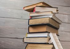 Ladder on pile of old books on wooden background stock images