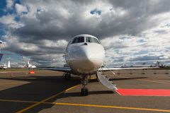 Ladder in a private jet. White reactive private jet, the front landing gear and a ladder on blue sky and clouds Royalty Free Stock Photo