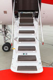 Ladder in a private jet. White private jet and open ladder with red carpet at the airport Stock Image