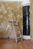 A ladder in the room during the repair. With shabby wall and black stove in the corner royalty free stock photography