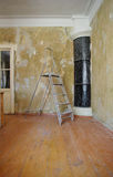 A ladder in the room during the repair. With shabby wall and black stove in the corner stock photos