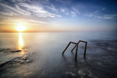 Ladder in the sea in front of the sunrise Stock Images