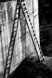 Ladder and shadows.. Black and white image of a propped up ladder with its cast shadow against the wall.  Beautiful composition with detail to texture and use Stock Image