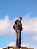 Ladder in the sky. The young man stands on the top degree of a ladder royalty free stock photography