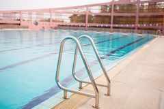 Ladder stainless handrails for descent into swimming pool. Swimming pool with handrail. Ladder of a swimming pool. Horizontal shot stock photos