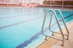Ladder stainless handrails for descent into swimming pool. Swimming pool with handrail . Ladder of a swimming pool. royalty free stock image