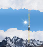 Ladder of success. Businessman standing on ladder high above mountain scene Stock Photo