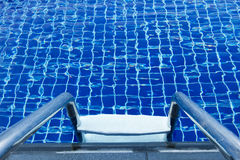 Ladder of a swimming pool. With blue water and refreshing. For background Royalty Free Stock Photo