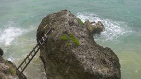 A ladder to a rock just offshore in the sea. High angle view looking down at a wooden ladder leading to a rock just offshore a cliff on the coastline of stock video