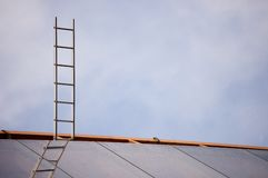 Ladder to the sky. A ladder to the sky on top of modern building roof stock images