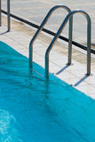 Ladder to swimming pool. Metal ladder to swimming pool with blue water Stock Photos