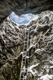 Ladder in a vertical tunnel in the mountains and the sky in a sk Stock Photo