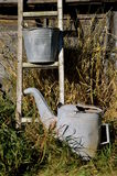 Ladder, water sprinkler, and a pail. On an old wooden ladder is a galvanized pail and a sprinkler can for watering plants royalty free stock photography