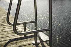Ladder on wooden dock by sea Stock Images