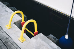 Ladder on a wooden pier beside a yacht. Yellow ladder on a wooden pier beside a yacht in Sopot Royalty Free Stock Photos