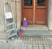 Ladders, bucket and brush. Ready for cleaning house: ladders, bucket and brush in front of the entrance stock image
