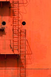 Ladders on the Container Ship. Ladders and platforms against the orange wall of a Container Ship royalty free stock photography