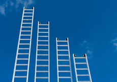 Ladders. A gradient of aluminum ladders stock photos