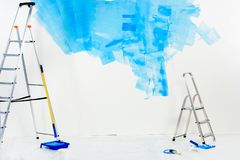 Ladders and paint roller brushes in blue. Paint stock image