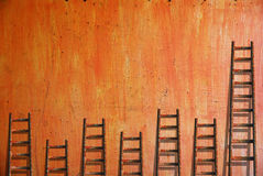 Ladders on red wall. Competition concept stock photo