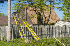 Ladders. Two ladders on a wood fence with a roof in the background on a blue sky royalty free stock photo