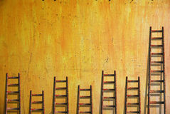 Ladders on yellow wall Stock Image