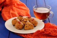 Laddu besan del vegano e tè nero sulla tavola blu profonda Immagine Stock