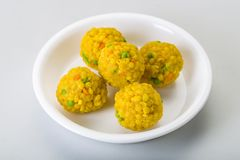 Laddu or laddoo are ball-shaped sweets popular in the Indian subcontinent. Laddus are made of flour, minced dough and sugar with other ingredients that vary by stock image