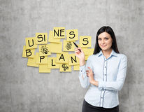 Lade shows the new business plan. Yellow stickers are hanged on the concrete wall. Brunette lade shows the new business plan. Yellow stickers are hanged on the Stock Photos