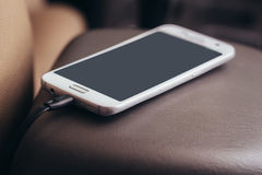 Ladegerätsteckertelefon auf Auto Stockfotografie