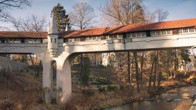 Ladek Zdroj - puente cubierto sobre el río en parque de la ciudad Foto de archivo libre de regalías