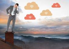 Laden Sie Wolke Ikonen und Geschäftsmann, die auf Dach mit Kamin und nebelhafter bunter Himmellandschaft stehen Stockbild