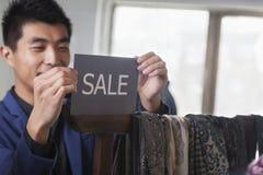 Ladenangestellter, der für Verkaufszeichen am Modespeicher aufstellt Stockbild