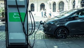 Ladend echte elektrische auto op de straat wat de toekomst van de Auto zijn stock afbeelding
