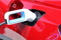 Ladend een rode EV elektrische auto bij het laden post, Toekomst van vervoer stock foto's