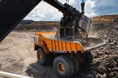 Ladender großer gelber Bergbau-LKW Stockfotos