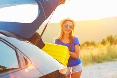 Ladengepäck der jungen Frau in die Rückseite des Autos Stockbild
