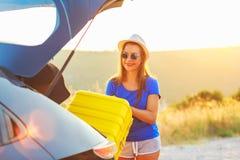 Ladengepäck der jungen Frau in die Rückseite des Autos Stockfotografie