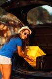 Ladengepäck der jungen Frau in die Rückseite des Autos Stockfoto