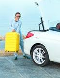 Ladengepäck der jungen Frau in die Rückseite des konvertierbaren Autos Lizenzfreies Stockfoto