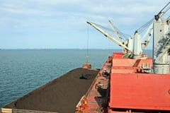 Ladenkohle von der Fracht barges auf ein Massengutschiff, das Schiffskräne und -zupacken am Hafen von Samarinda, Indonesien verwe stockfotografie