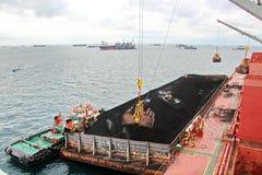 Ladenkohle von der Fracht barges auf ein Massengutschiff, das Schiffskräne und -zupacken am Hafen von Samarinda, Indonesien verwe stockbild