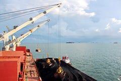 Ladenkohle von der Fracht barges auf ein Massengutschiff, das Schiffskräne und -zupacken am Hafen von Samarinda, Indonesien verwe stockbilder