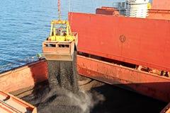 Ladenkohle von der Fracht barges auf ein Massengutschiff, das Schiffskräne und -zupacken am Hafen von Samarinda, Indonesien verwe lizenzfreie stockfotografie