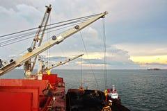 Ladenkohle von der Fracht barges auf ein Massengutschiff, das Schiffskräne und -zupacken am Hafen von Samarinda, Indonesien verwe lizenzfreies stockbild