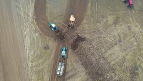 Lader-Eimer setzt Düngemittel herein des Anhänger-Traktors, um landwirtschaftliches Feld zu behandeln stock video footage