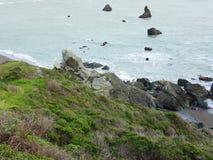 Ladera y rocas del verde de California en la orilla - viaje por carretera a lo largo de la carretera costera ningún 1 Imágenes de archivo libres de regalías